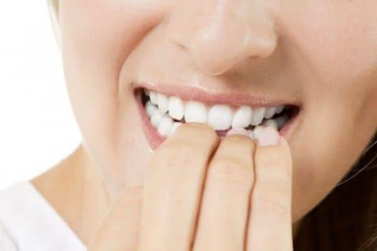 Cắn móng tay gây hại răng